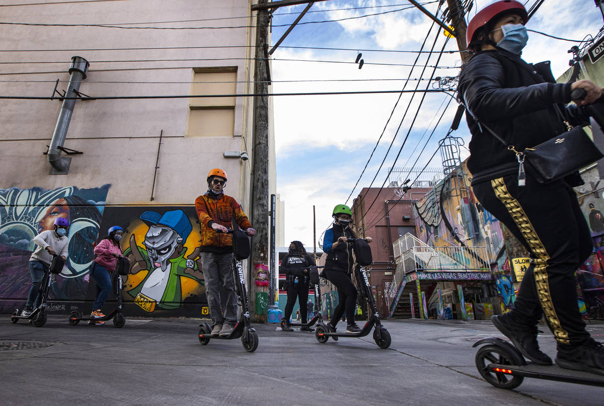 A tour group with Atomic Scooters passes by a new tribute to rapper MF Doom by artist Spen.1 an ...