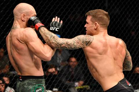 ABU DHABI, UNITED ARAB EMIRATES - JANUARY 23: (R-L) Dustin Poirier punches Conor McGregor of Ir ...