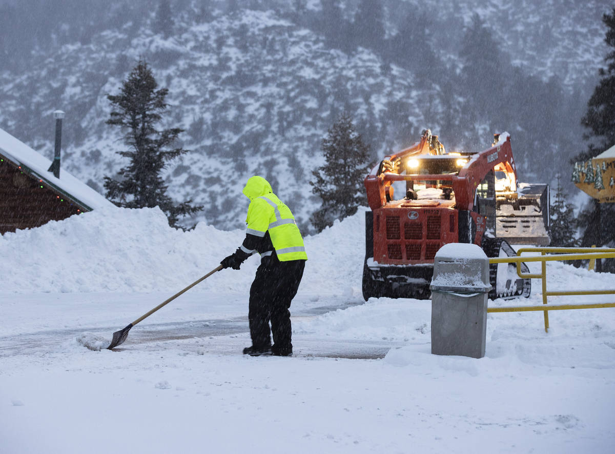 Workers remove snow from the parking lot at The Charleston Lodge, on Monday, Jan. 25, 2021, in ...