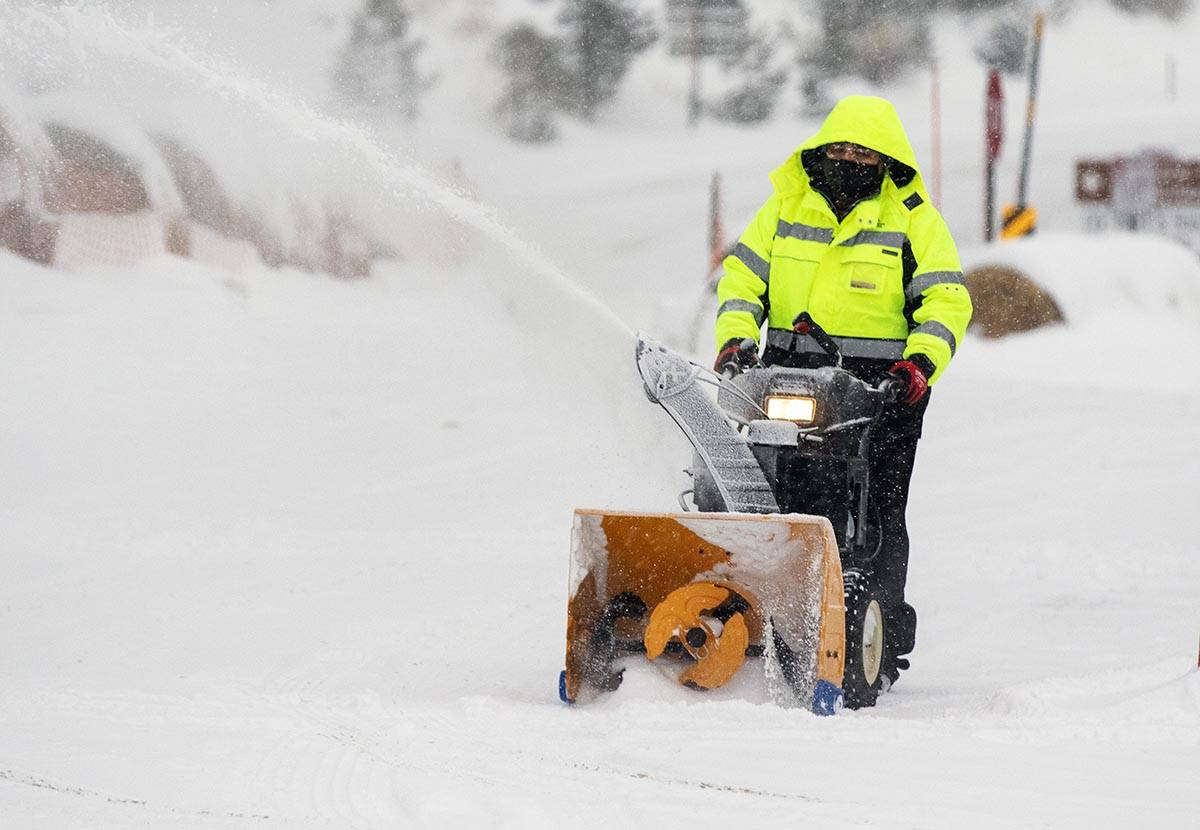 Pedro Diaz clears snow with a snow blower from The Charleston CabinÕs parking lot, on Mond ...