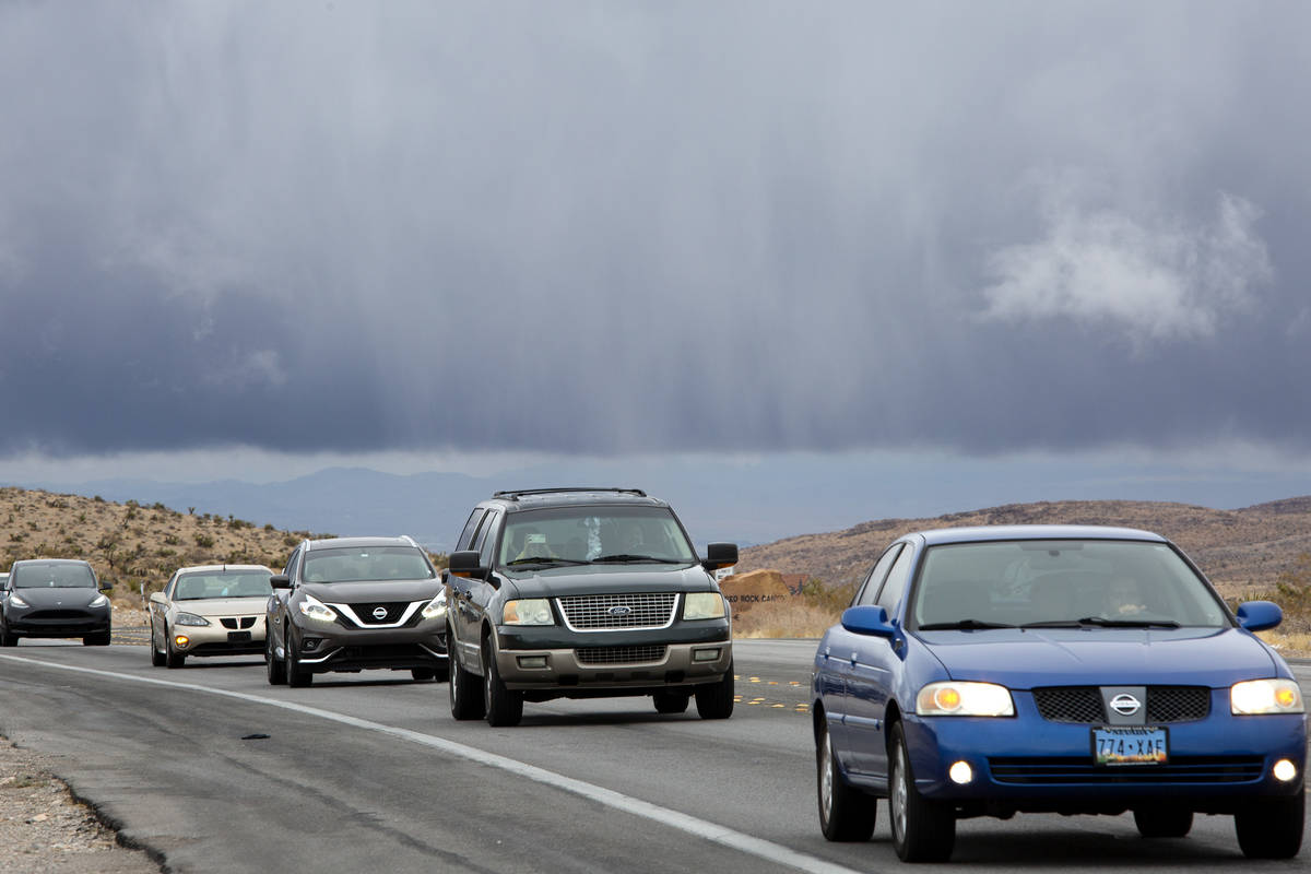 Dark clouds hover over the Las Vegas Valley as visitors drive into Red Rock National Conservati ...