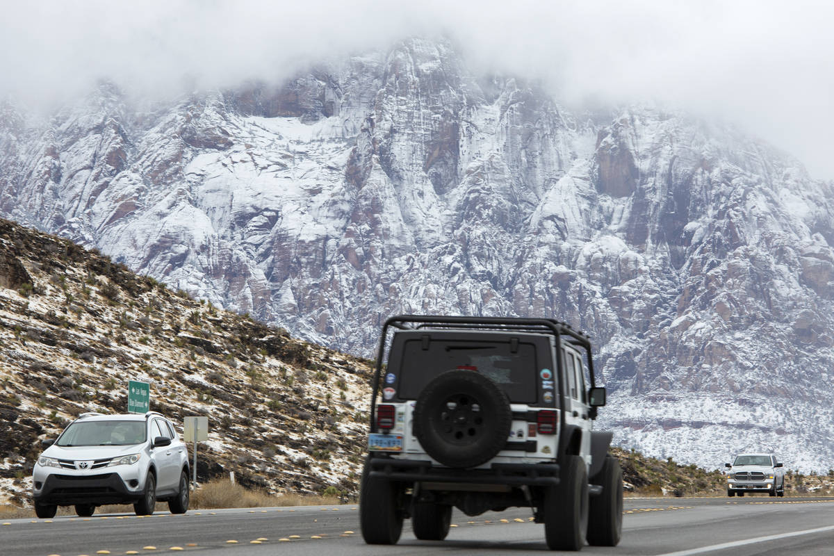 Visitors drive through Red Rock National Conservation Area as snow covers the mountains on Mond ...