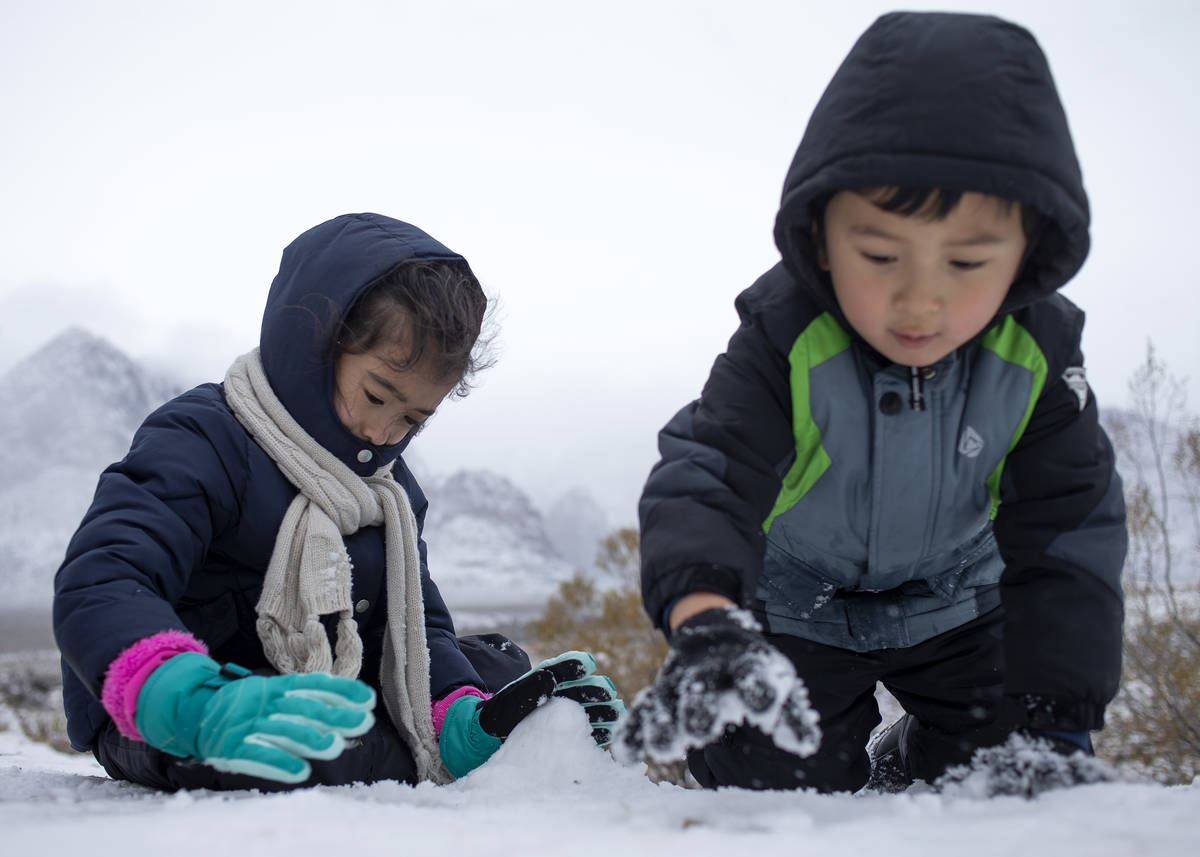 Iliana Lopez, 6, left, and her brother Sasha Lopez, 4, build a snow mountain to match the mount ...