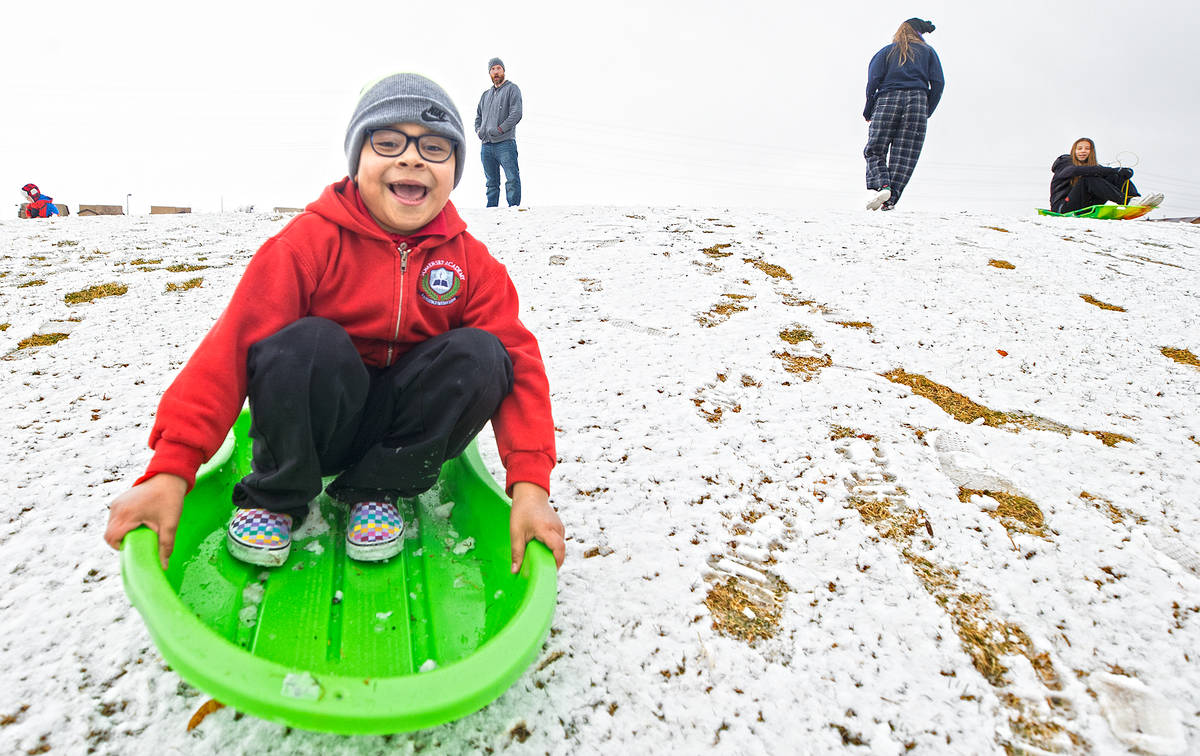 Gabriel Prieto, 8, sleds down a hill at Knickerbocker Park on Monday, Jan. 25, 2021, in Las Veg ...