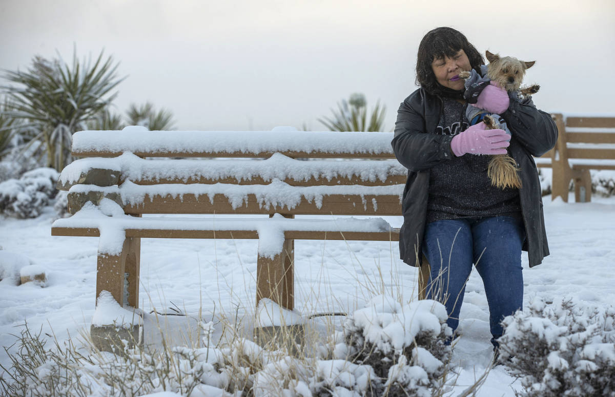 Charonn Williams sits with her dog Snickers up on the overlook as the clouds break on a snowy d ...