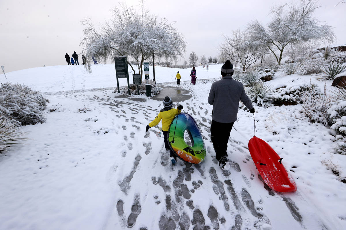 Colton Tarantino, 5, and his father Nick prepare to play in the snow at Fox Hill Park in Summer ...
