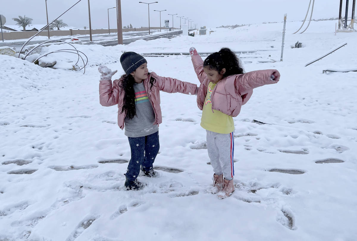 Kelly Sanchez, 7, left, and her sister Kyara, 5, play in freshly fallen snow at the intersectio ...