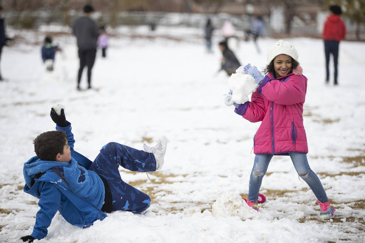Cash' Mir Segovia, 7, gets ready to throw a snowball at her brother King, 7, at Huckleberry Par ...