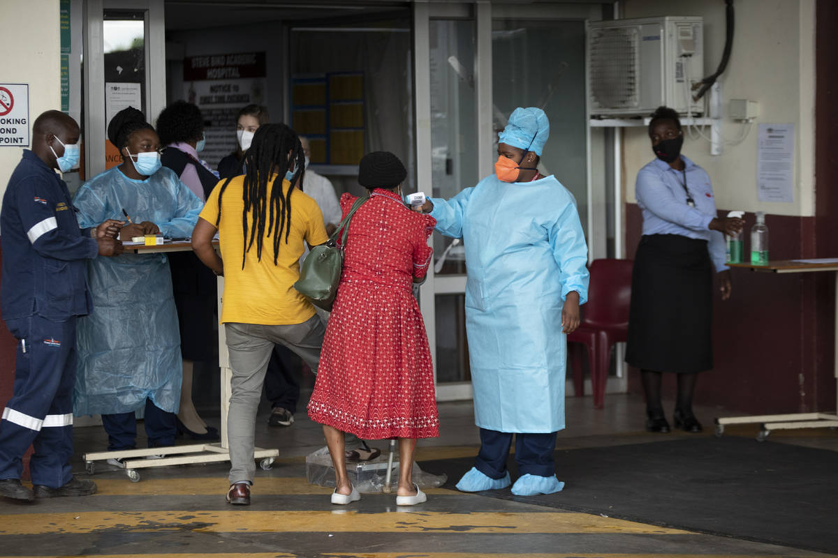 A health worker checks the temperature of an elderly patient at the emergency entrance of the S ...