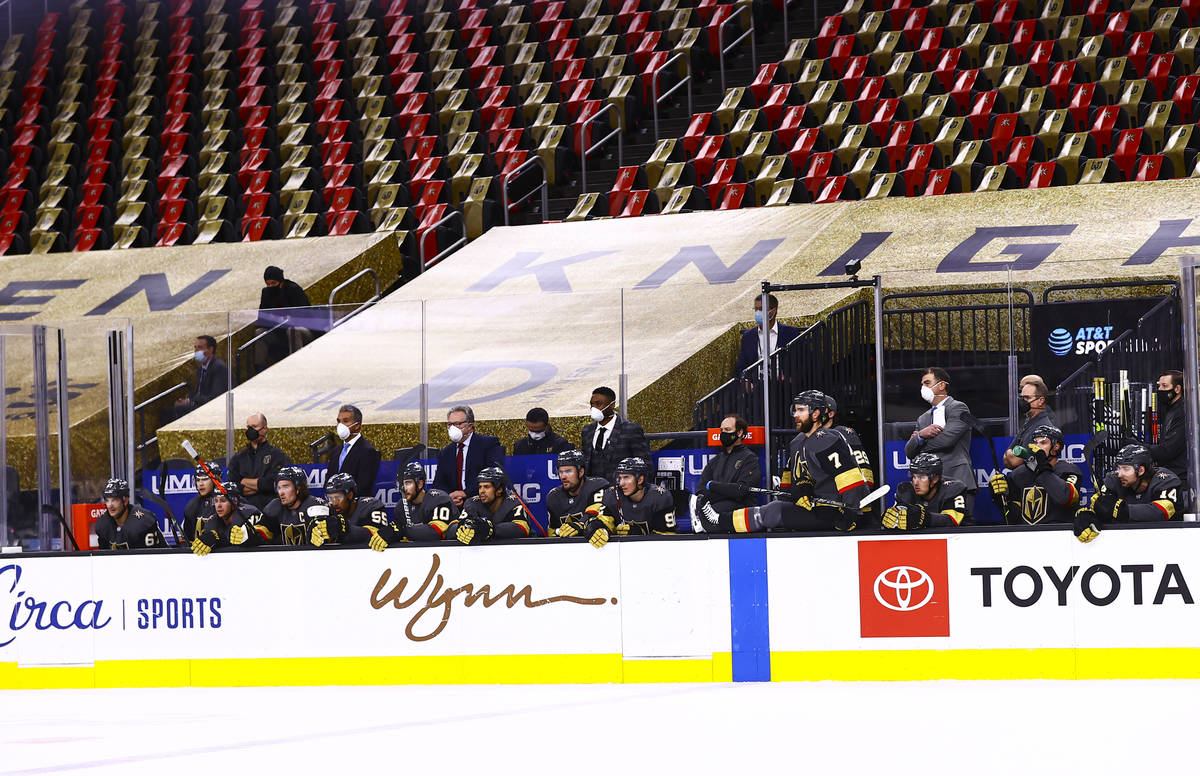 Empty seats are seen behind the Golden Knights bench during the first period of an NHL hockey g ...