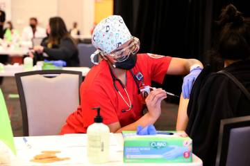 Nursing student Alaysia Robinson gives a COVID-19 vaccine during a UNLV Medicine clinic in the ...