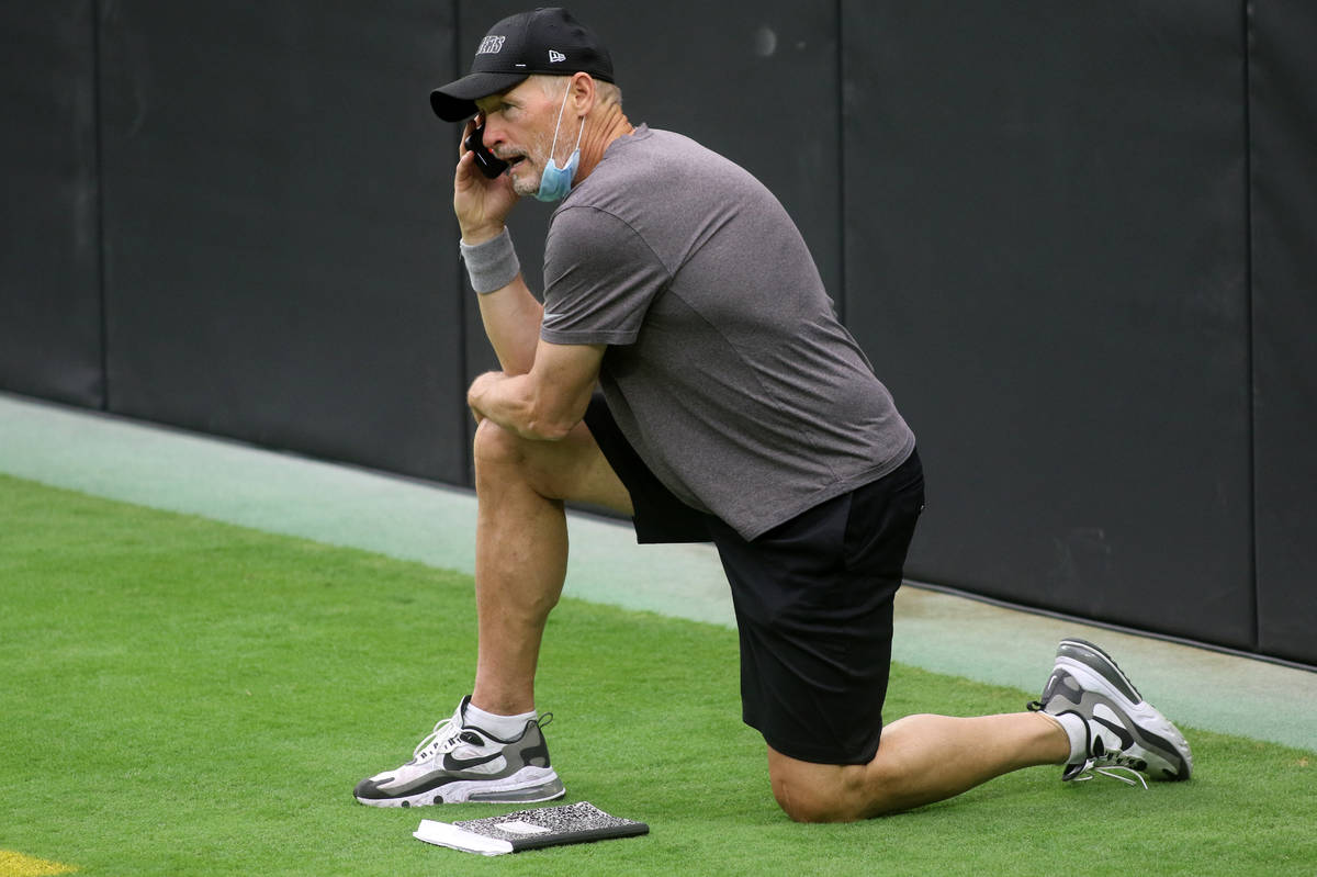 Las Vegas Raiders general manager Mike Mayock takes a phone call prior to a team practice at Al ...