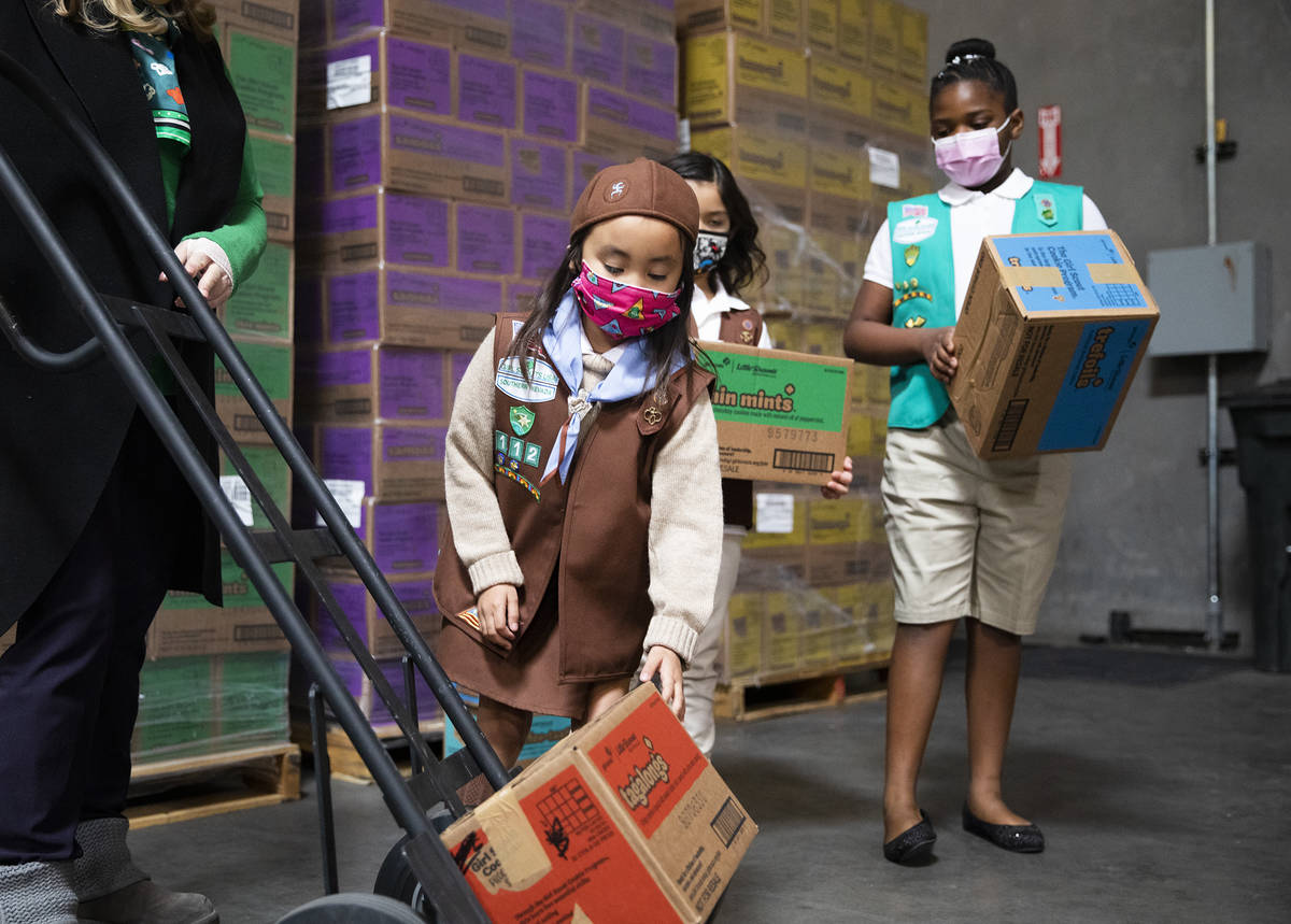 Girl scouts Penelope W., 7, moves a box of Girl Scout Cookies onto a dolly held by Kimberly Tru ...