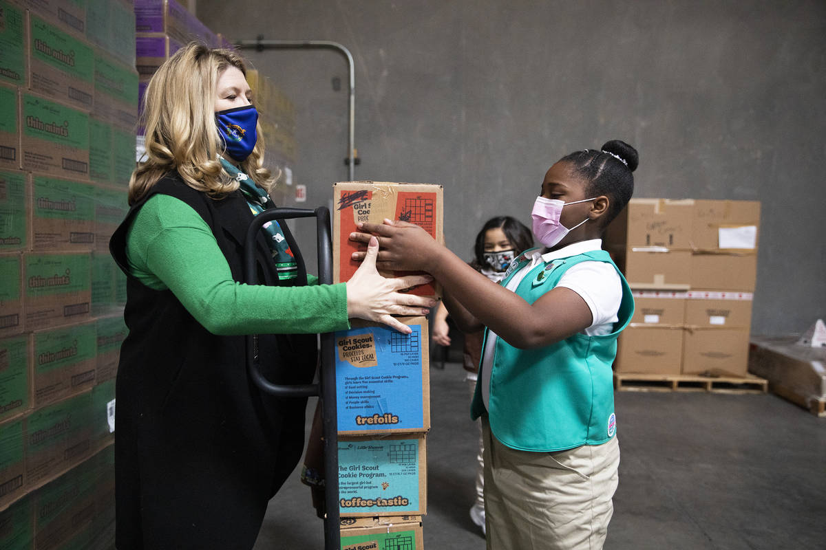 Girl Scout Aliyah H., 9, moves a box of Girl Scout Cookies onto a dolly held by Kimberly Trueba ...