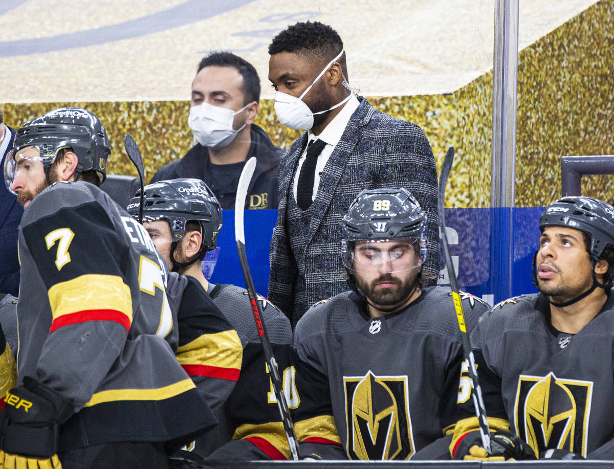 Silver Knights assistant coach Joel Ward, center, looks on from the Golden Knights bench during ...
