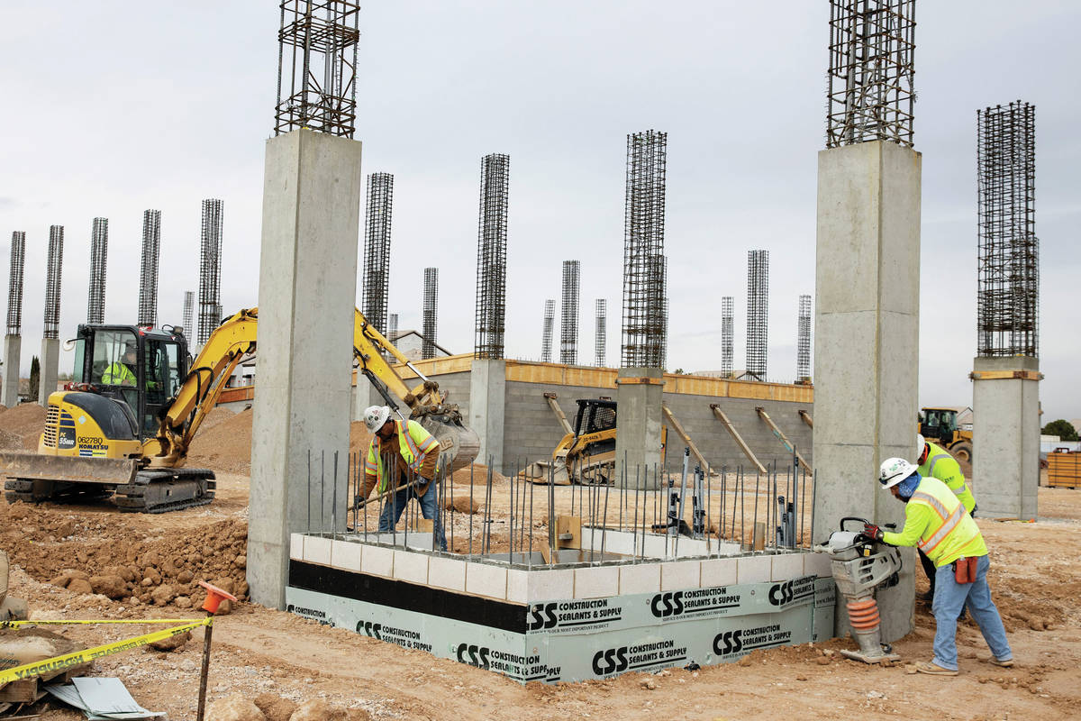 Construction workers use compactors to firm soil at the construction site of Axiom, an office c ...