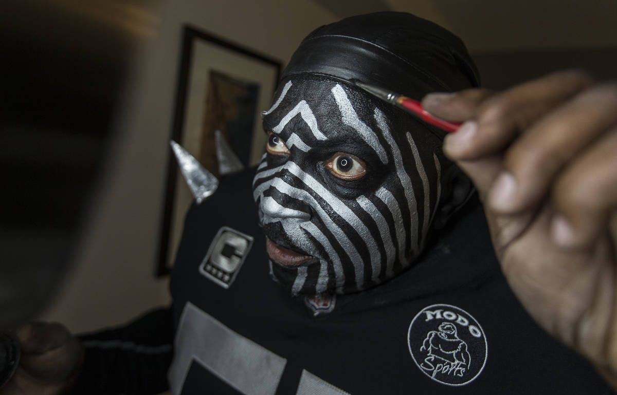 """Raiders super fan Wayne Mabry, known as """"Violator,"""" applies makeup in his hotel room at 4 a.m. ..."""