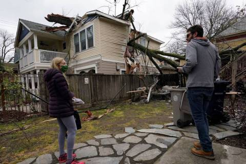 Amy Lilly talks with neighbor Eric Rose as they look over her home damaged by a tree limb that ...