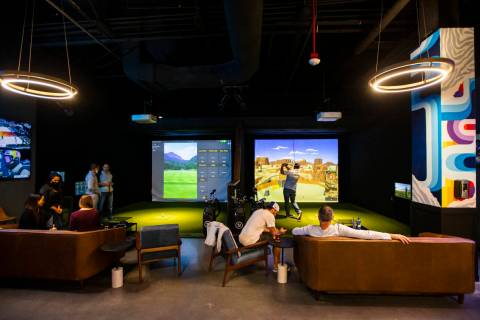 People mingle and take turns playing during a friends and family event at Five Iron Golf at Are ...