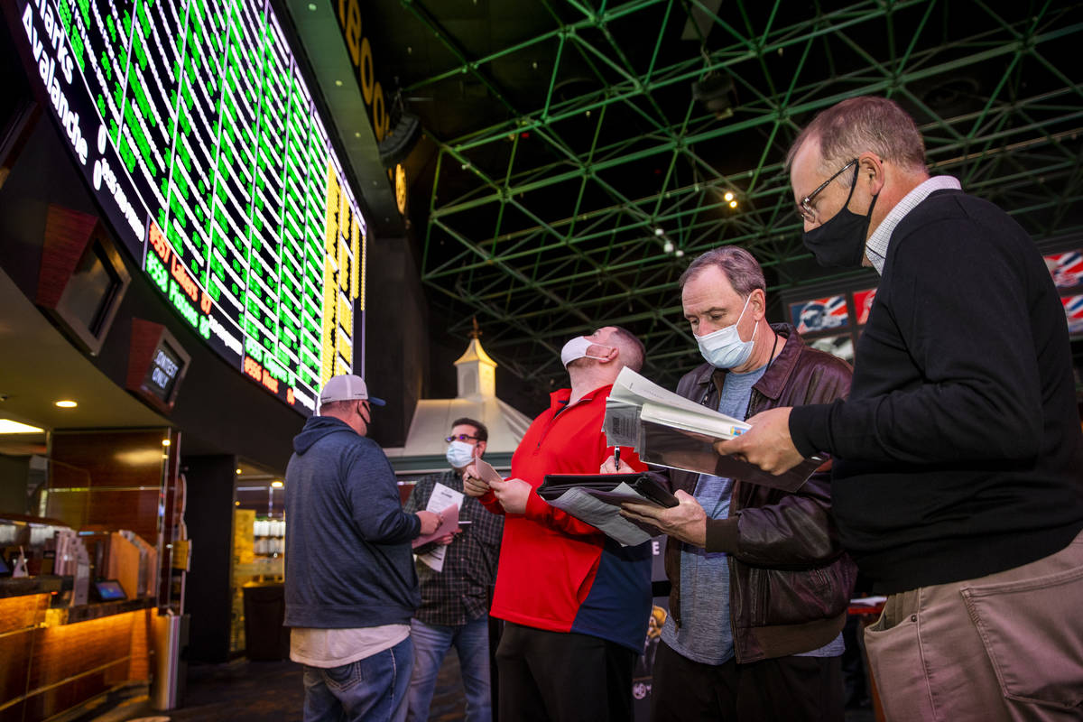 (From left) Bettors James, Jimmy and Logan Fields go over the numbers in line as the Westgate s ...