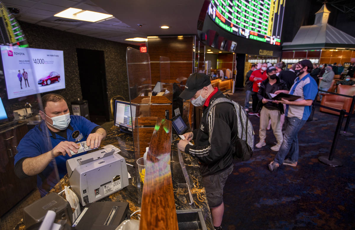 Mike Iannone, left, counts cash placed by a bettor as the Westgate sportsbook posts hundreds of ...