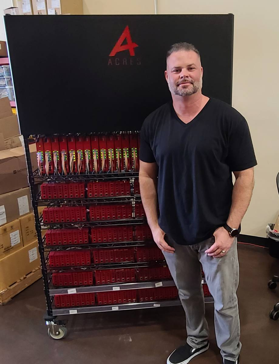 Noah Acres of Acres Technology stands in front of a bank of Foundation system units at the comp ...