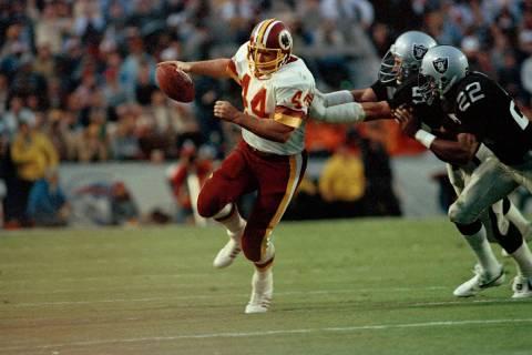 Washington Redskins running back John Riggins is pursued by Los Angeles Raiders defenders inclu ...
