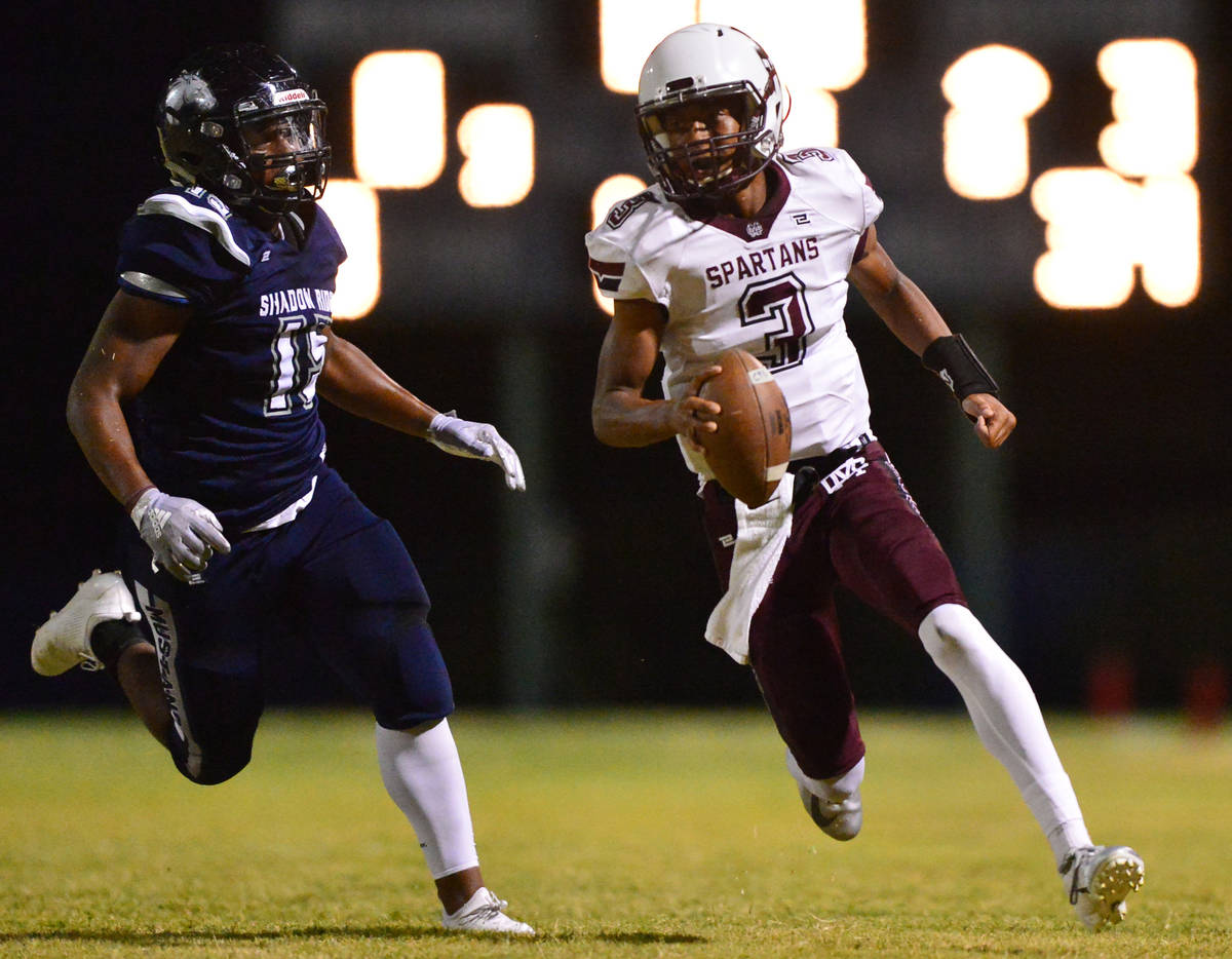 Cimarron-Memorial quarterback Branden Smith (3) is chased down by Shadow Ridge defensive end Is ...
