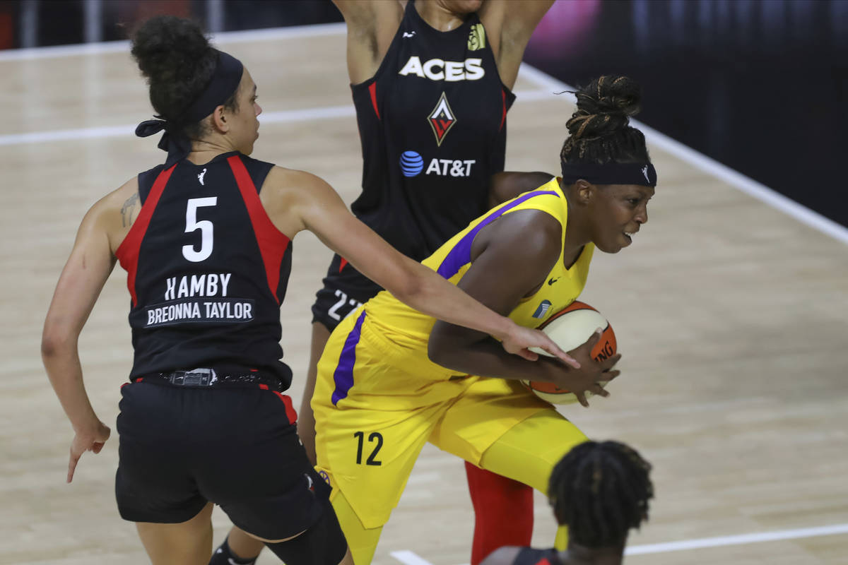 Los Angeles Sparks' Chelsea Gray (12) drives past Las Vegas Aces' Dearica Hamby during the seco ...