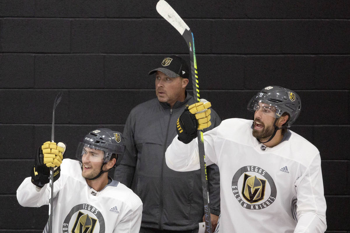 In this July 20, 2020, file photo, Golden Knights' assistant coach Steve Spott, center, is seen ...