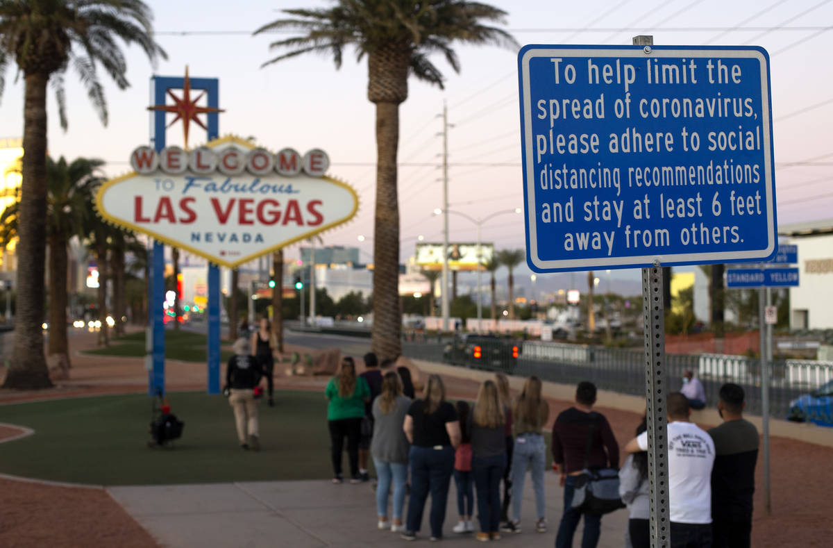 A sign asks visitors to stand apart to prevent the spread of coronavirus as they wait in line t ...