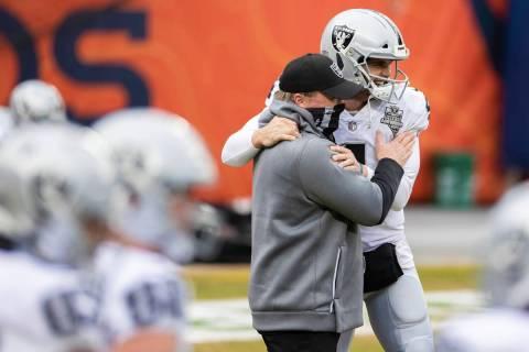 Raiders head coach Jon Gruden, left, hugs Raiders quarterback Derek Carr (4) during warm ups be ...