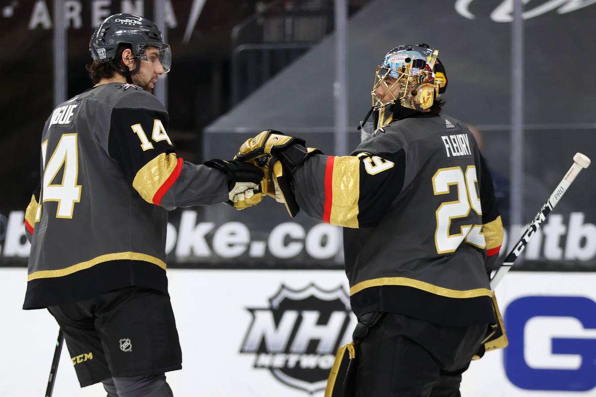 Vegas Golden Knights defenseman Nicolas Hague (14) and goaltender Marc-Andre Fleury (29) bump g ...