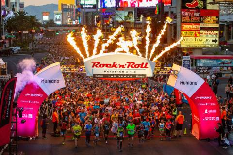 Runners leave the starting line beneath flames during the Rock 'n' Roll Marathon Sunday, Nov. 1 ...