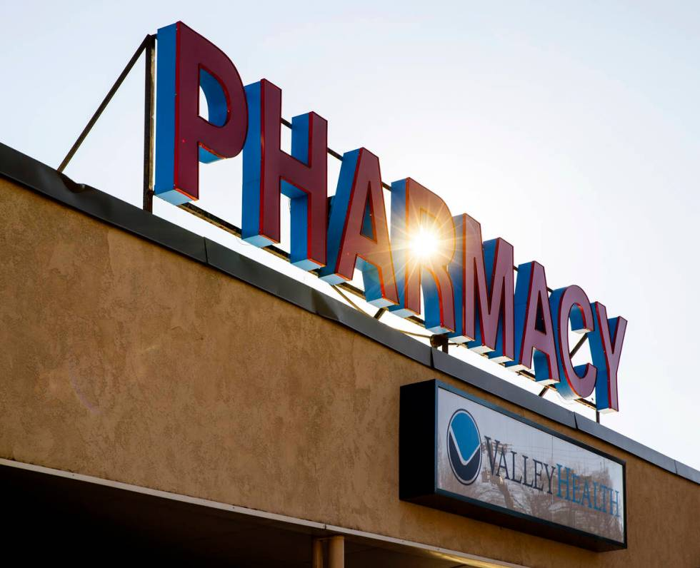 The sun rises behind a Fruth pharmacy sign on Wednesday, Feb. 3, 2021, in Charleston, W.Va. (L. ...