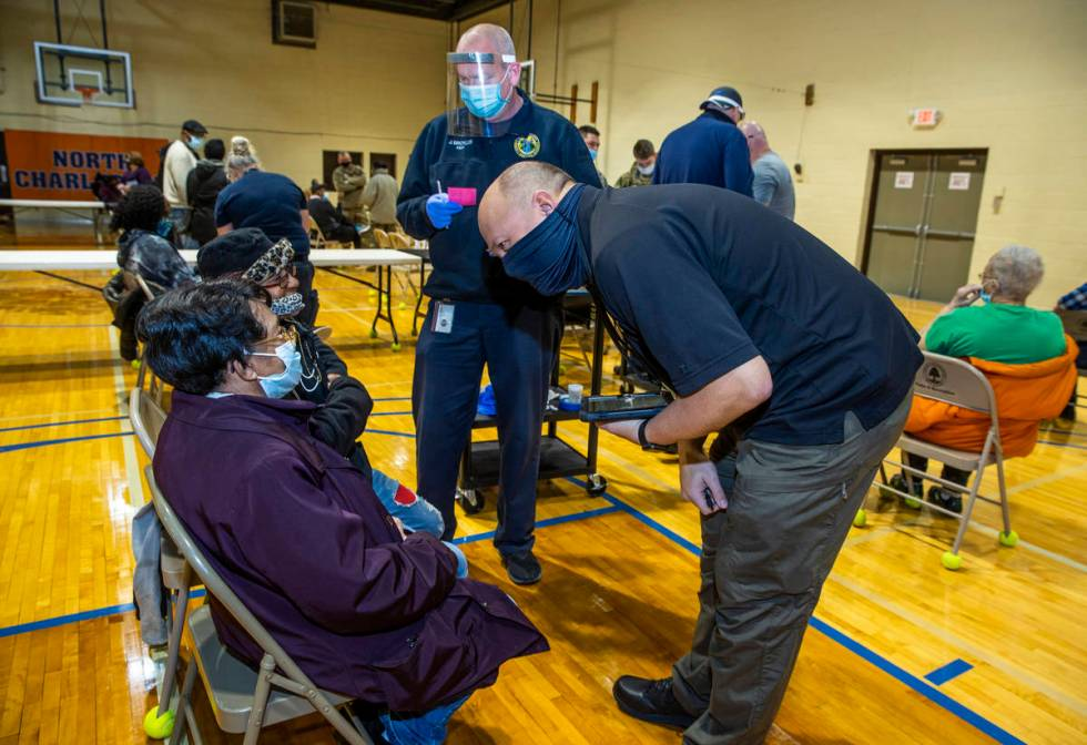 (From right) Sheriff's officer Doug Beasley and Kanawha County EMT Jeff Broyles team up to deli ...