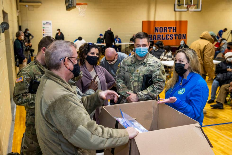 Dr. Sherri Young, right, confers with West Virginia Guardsmen and Kanawha County personnel as t ...