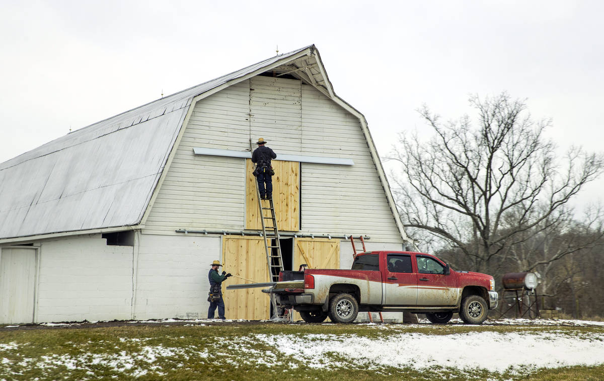 Men replace barn doors and a farm on Thursday, Feb. 4, 2021, near Southside, W.Va. (L.E. Baskow ...
