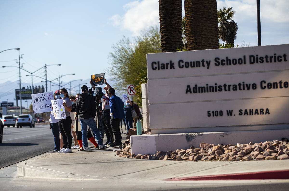 Student athletes and parents participate in a rally to urge school district officials to bring ...