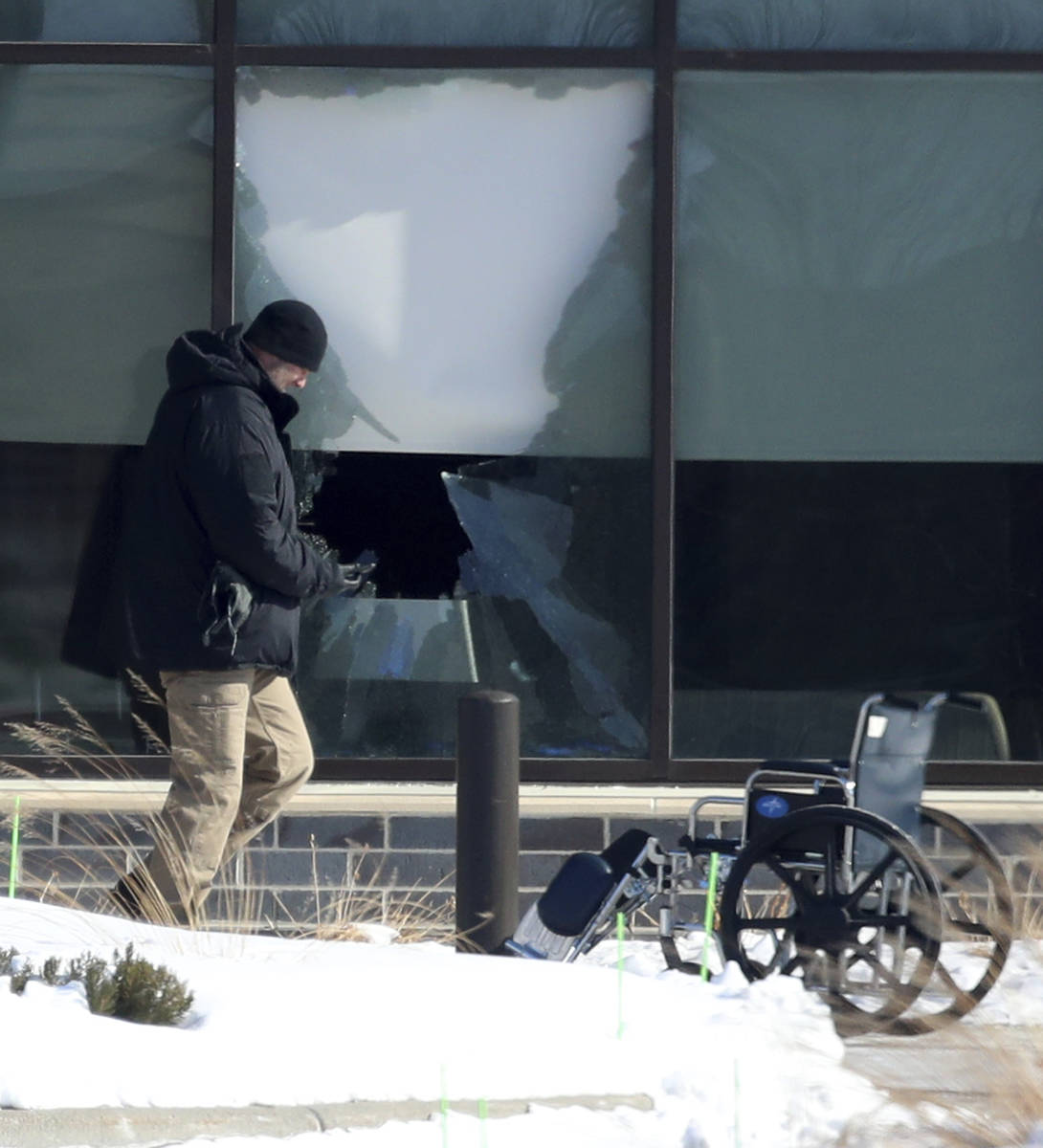 Law enforcement personnel walk past a broken window outside of the Allina Health clinic, Tuesda ...