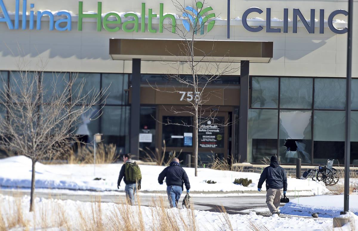 Law enforcement personnel walk toward the Allina Health clinic, Tuesday, Feb. 9, 2021, in Buffa ...