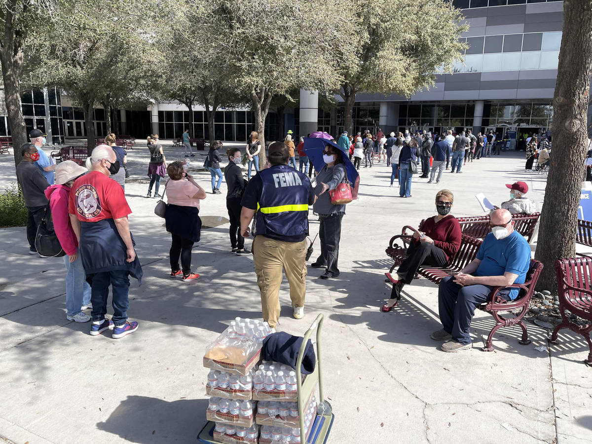 A worker hands out water to people in line for the second dose of the COVID-19 vaccine outside ...