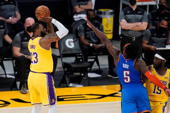 Los Angeles Lakers forward LeBron James (23) makes a 3-pointer against the Oklahoma City Thunde ...