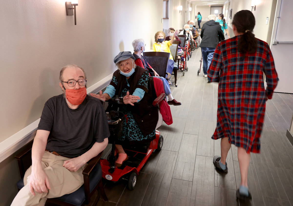 Michael Chernoff, 65, and Valmae Ayres, 98, wait in line for the COVID-19 vaccine during an in- ...