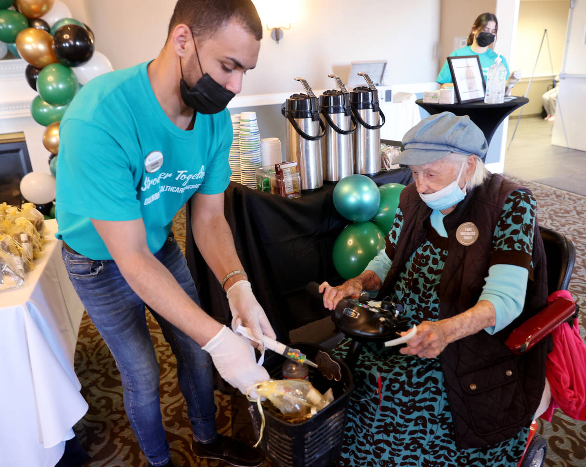 Quintan Brown-Rodrigues gives Valmae Ayres, 98, treats, including a syringe filled with candy, ...