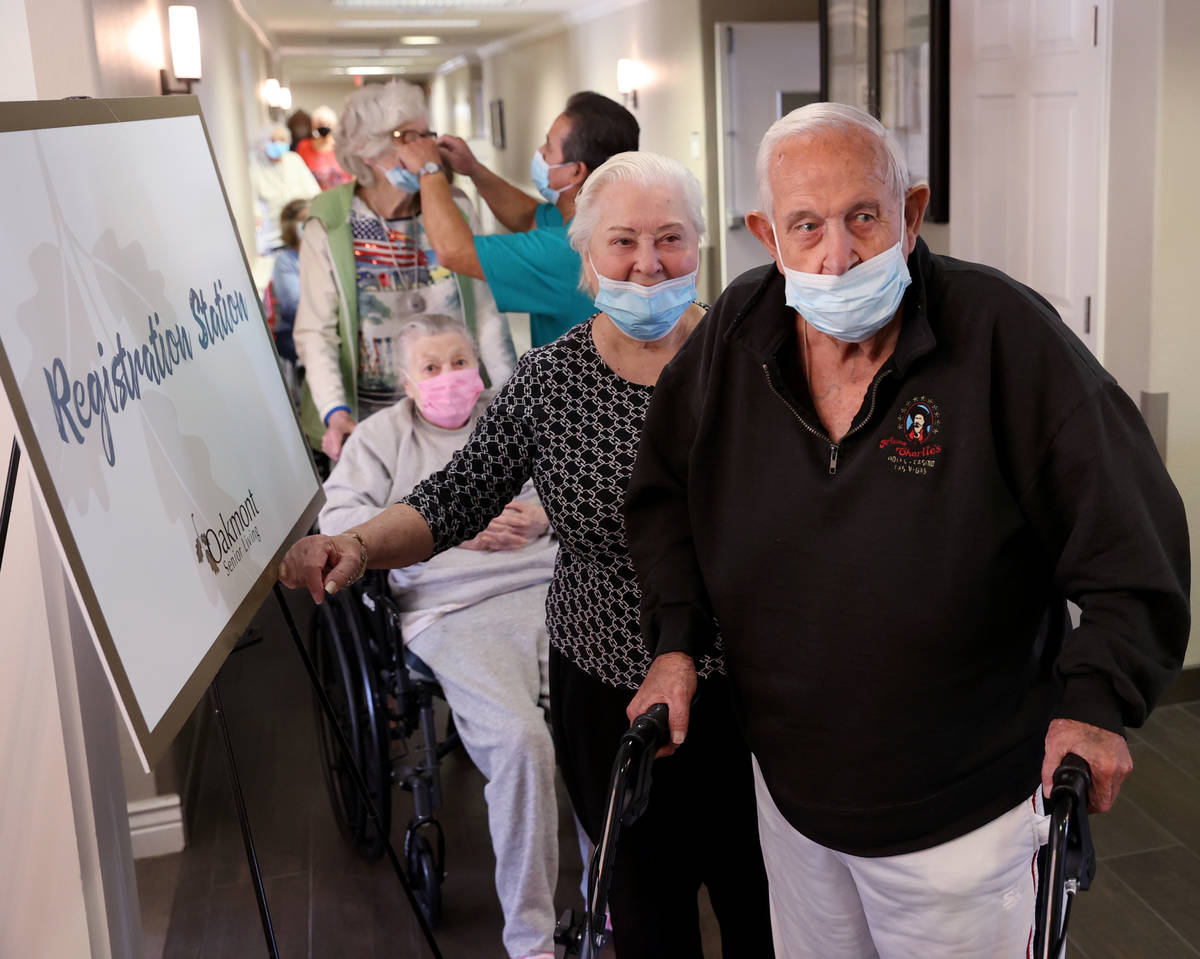 Don Masterson, 90, and Darlene Cox, 91, wait in line for the COVID-19 vaccine during an in-hous ...