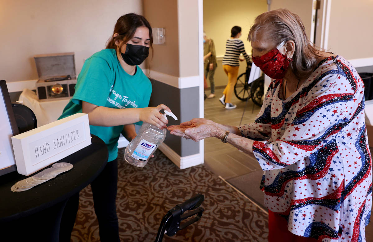 Server Alondra Chavarria gives Beverly Winterboer, 87, hand sanitizer during an in-house COVID- ...