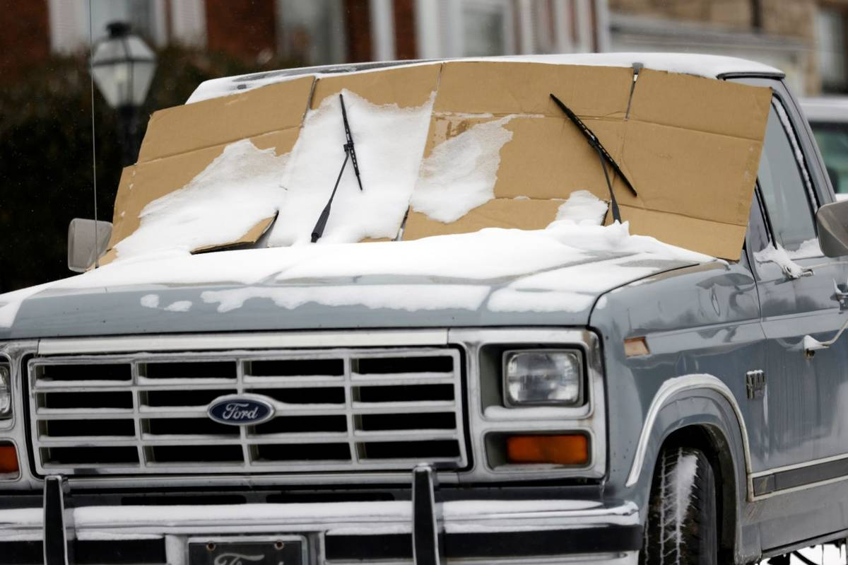 A resident of Tulsa takes precautions against an icy windshield as a winter storm moves into no ...