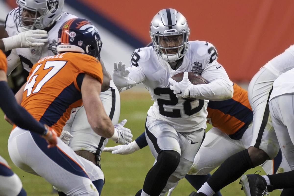 Raiders running back Josh Jacobs (28) burst through a hole past Denver Broncos inside linebacke ...
