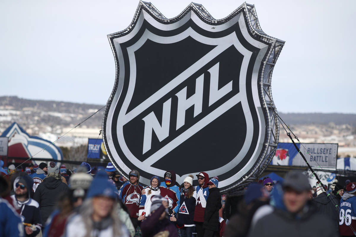 FILE - In this Feb. 15, 2020, file photo, fans pose below the NHL league logo at a display outs ...